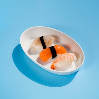 Tazón ovalado blanco con sushi sobre un fondo azul.