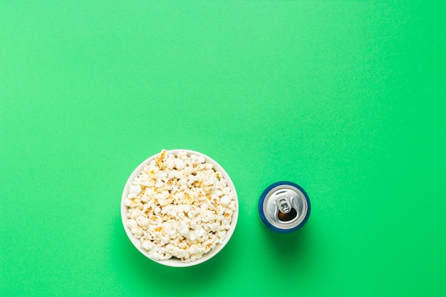 Tazón con palomitas de maíz y una lata de bebida sobre un fondo verde. el concepto de ver películas y programas de televisión favoritos, competiciones deportivas. vista plana, vista superior.