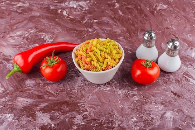 Un tazón de pasta espiral cruda multicolor con tomates rojos frescos y ají.