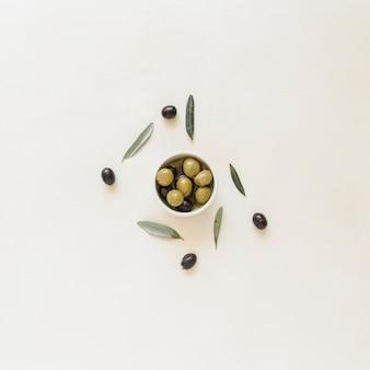 Tazón pequeño con aceitunas y hojas