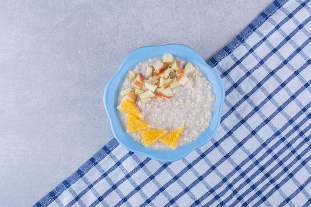 Tazón pequeño de avena sobre una toalla cubierta con trozos de naranja y manzana picada, sobre una superficie de mármol