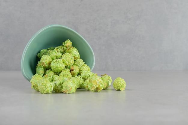 Tazón pequeño caído, derramando palomitas de maíz confitadas verdes sobre fondo de mármol.