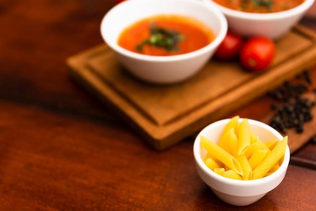 Tazón pequeño de pasta penne cruda en la mesa con salsas desenfocadas y tomates sobre tabla de madera