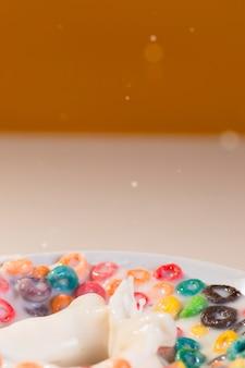 Tazón de primer plano con cereales y leche en la mesa