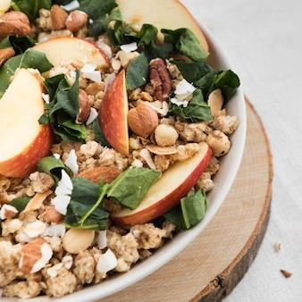 Tazón de primer plano lleno de cereales y rodajas de manzana