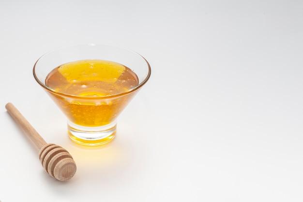 Tazón de primer plano con miel y palo