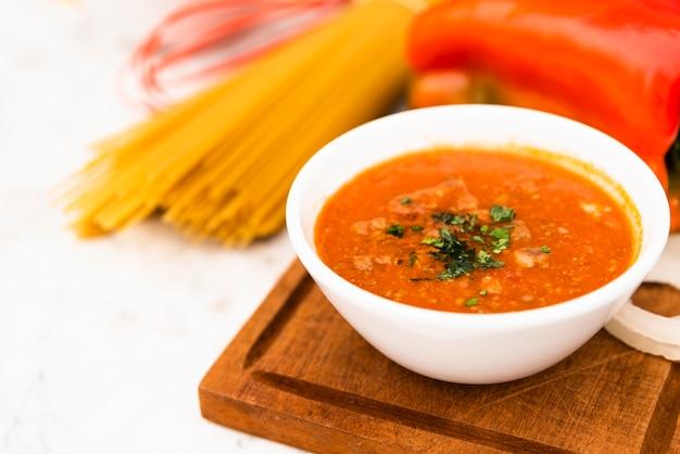 Tazón de sabrosa salsa de tomate sobre tabla para cortar madera