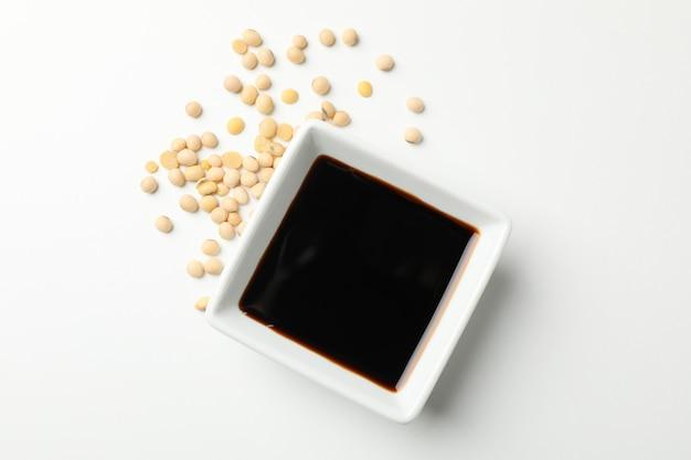 Tazón de salsa de soja, soja sobre fondo blanco, espacio para texto. vista superior
