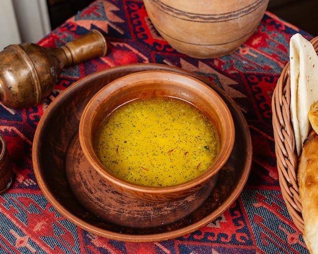 Un tazón de sopa de albóndigas dushbara adornado con hojas secas de menta