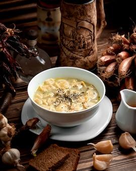 Tazón de sopa de albóndigas dushbara azerbaiyana adornado con menta seca