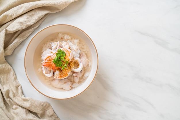 Tazón de sopa de avena o arroz hervido con mariscos (camarones, calamares y pescado)