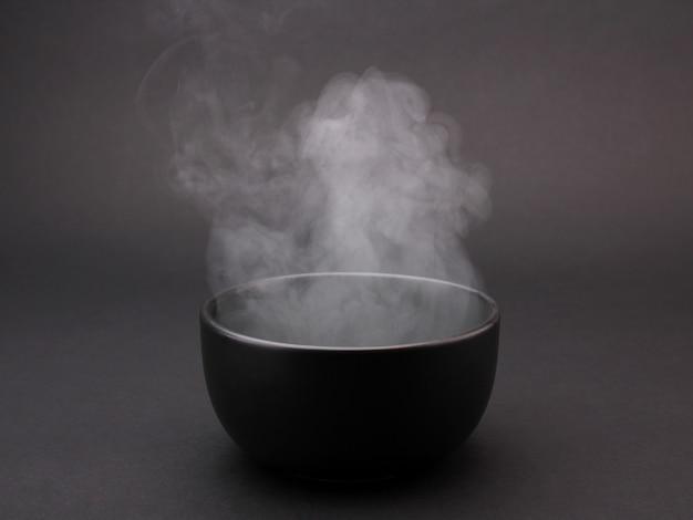 Tazón de sopa caliente sobre negro