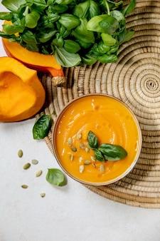 Tazón de sopa de crema vegetariana de calabaza o zanahoria decorada con albahaca fresca