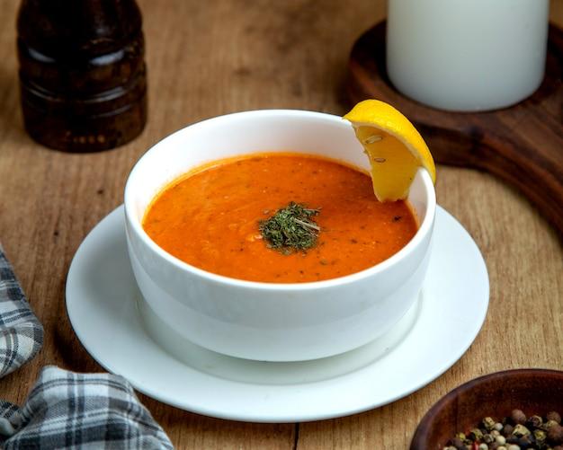 Un tazón de sopa de lentejas adornado con una rodaja de limón