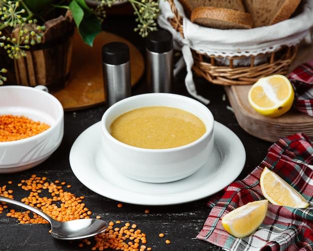 Tazón de sopa de lentejas servido con rodajas de limón