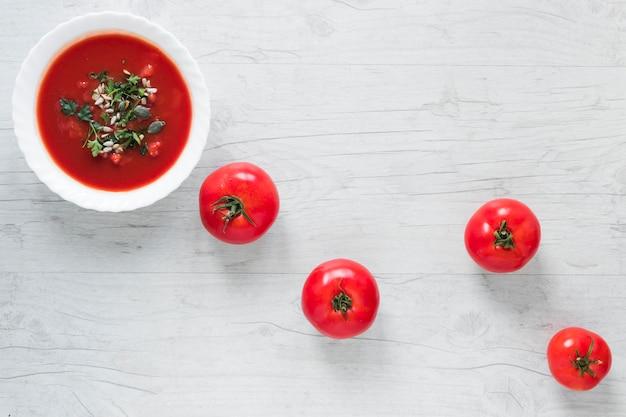 Un tazón de sopa de tomate fresco en un tazón de cerámica blanco adornado con hierbas y tomates maduros en mesa de madera