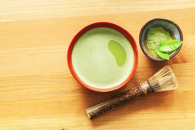 Un tazón de té matcha sobre una mesa de madera con un batidor y polvo con espacio de copia.