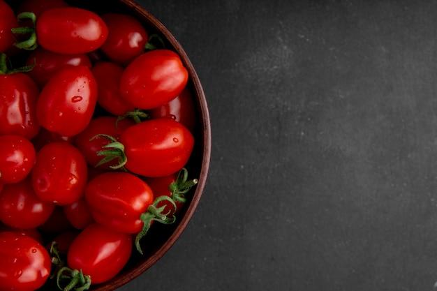 Tazón de tomates en el lado izquierdo sobre fondo negro