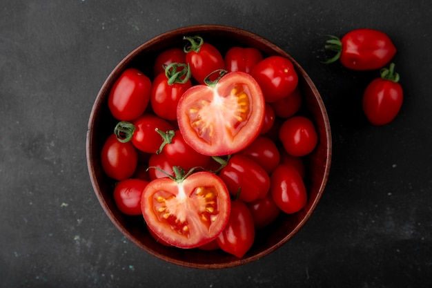 Tazón de tomates en superficie negra