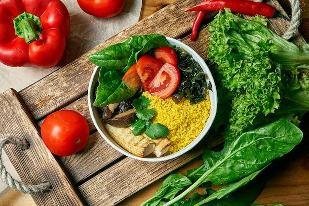 Tazón vegetariano con tomates cuscús, espinacas, queso de tofu y champiñones shiitaki en una bandeja de madera en una composición con verduras. vista superior comida plana lay
