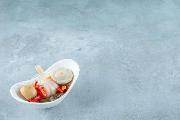 Un tazón de verduras fermentadas mixtas, sobre la mesa azul.