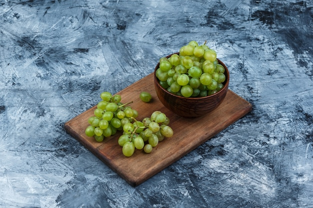 Tazón de vista de ángulo alto de uvas blancas en la tabla de cortar sobre fondo de mármol azul oscuro. horizontal