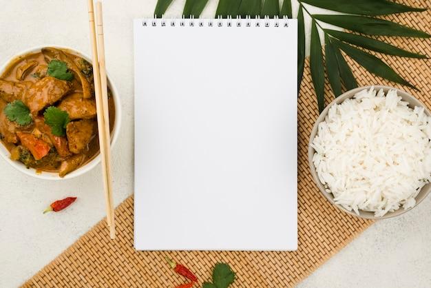 Tazón de vista superior de estofado casero y bloc de notas