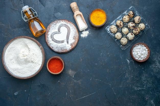 Tazón de vista superior con harina, tablero de madera, cúrcuma, pimienta y sal marina en tazones pequeños, huevos de codorniz, botella de aceite en la mesa, espacio libre