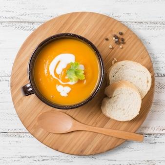 Tazón de vista superior con sopa de calabaza y pan