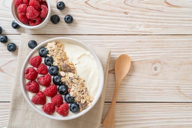 Tazón de yogur casero con frambuesa, arándano y granola - estilo de comida saludable