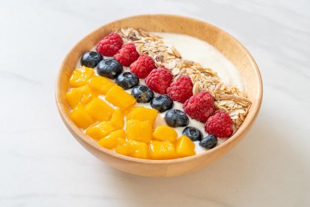 Tazón de yogur casero con frambuesa, arándano, mango y granola - estilo de comida saludable