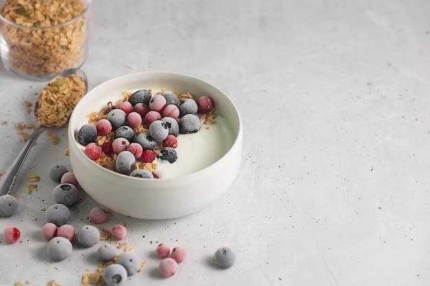 Tazón de yogur casero con granola y bayas congeladas cubiertas con escarcha sobre fondo gris, con espacio de copia