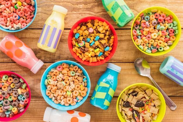 Tazones de cereales con botellas de leche y cuchara.
