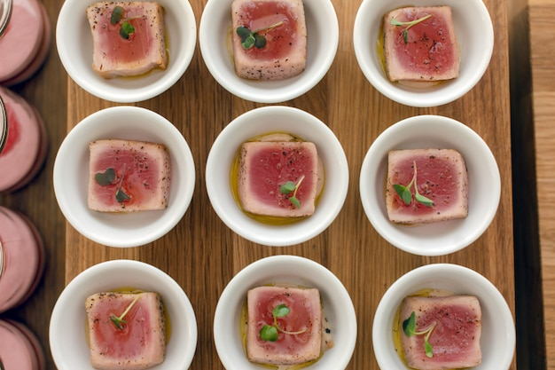 Tazones con deliciosos filetes de sintonía sobre tabla de madera