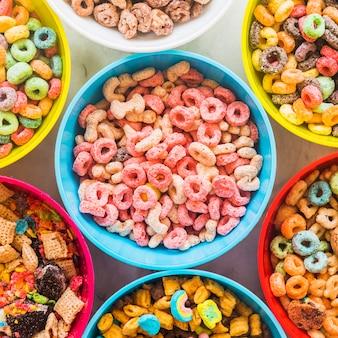 Tazones con diferentes cereales en mesa de luz.