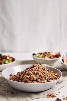 Tazones de granola con yogur, frutas y bayas sobre una superficie blanca