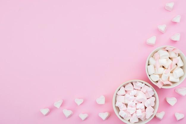Tazones con merengue sobre fondo rosa