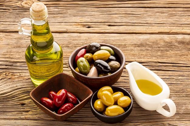 Tazones de oliva de alto ángulo, rebanadas de pan y aceite