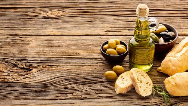 Tazones de olivo de alto ángulo, rebanadas de pan y aceite botte con espacio de copia