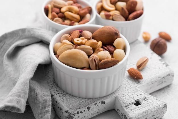 Tazones pequeños blancos llenos de variedad de nueces en la tabla de cortar