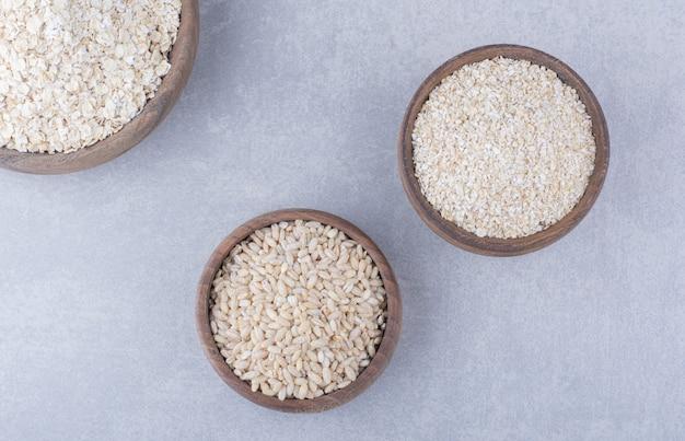 Tazones pequeños llenos de arroz, avena y copos de avena sobre superficie de mármol