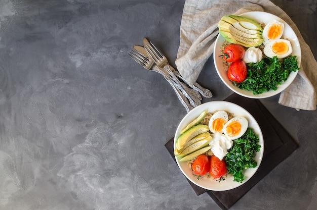 Tazones de quinoa buda con tomates al horno, aguacate, col rizada, huevos duros y yogur griego
