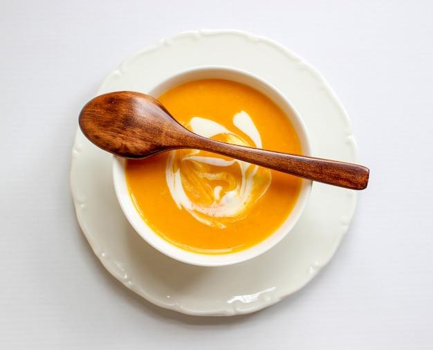 Tazones de sopa de calabaza sobre fondo blanco con tela gris y rodajas de calabaza