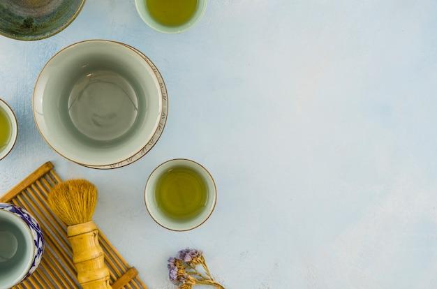 Tazones de té tradicionales y pincel de té sobre fondo blanco