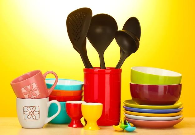 Tazones vacíos brillantes, tazas y utensilios de cocina en la mesa de madera sobre fondo amarillo