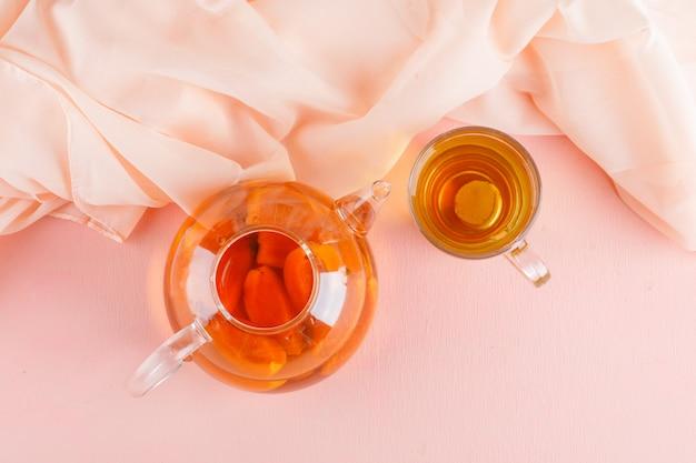 Té de albaricoque en tetera y taza de vidrio en mesa rosa y textil, vista superior.
