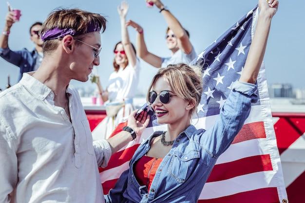 Te amo. encantadora chica sosteniendo la bandera americana mientras mira a su novio