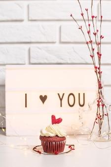 Te amo escrito en una lámpara decorativa junto a cupcakes rojos.