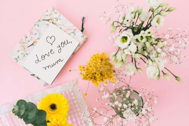 Te amo inscripción mamá con flores y cuaderno.