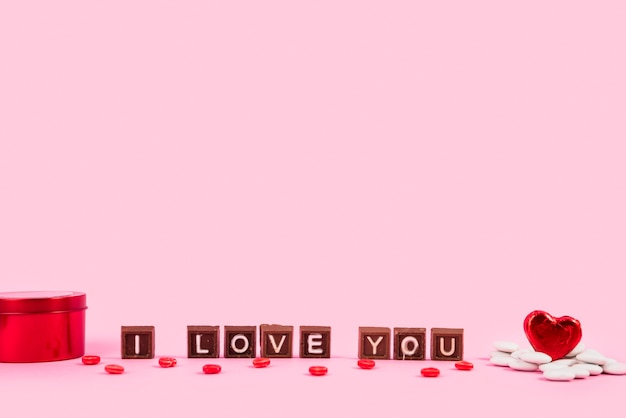 Te amo inscripción en trozos de chocolate entre caja y adorno de corazón.